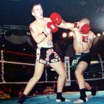 Steve Milles w zielonych spodenkach, pokazuje proste uderzenie i piękny przykład wbijania nóg, wypychając z tylnej stopy i nie wpadając na przeciwnika.